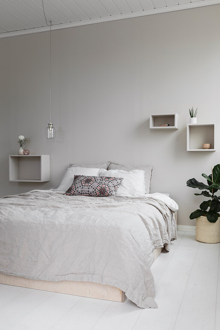 Double bed, shelves and pendant lamps in bright bedroom