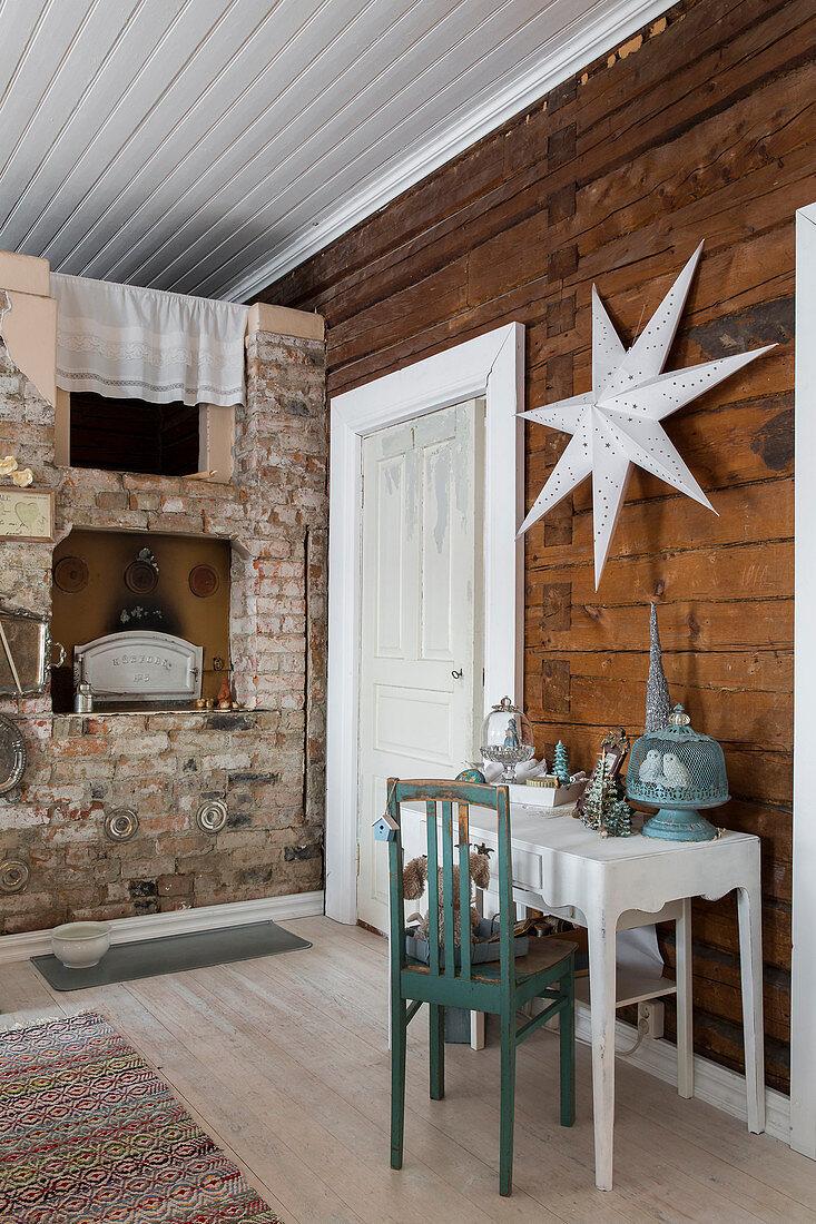Wandtisch vor Holzwand mit Sterndeko, im Hintergrund rustikaler Backstein-Kamin