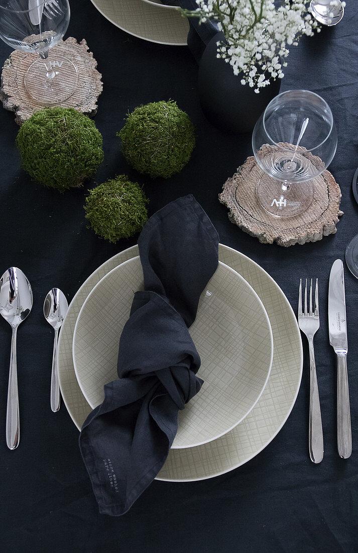 Table set with dark linens, beige crockery and handmade moss balls