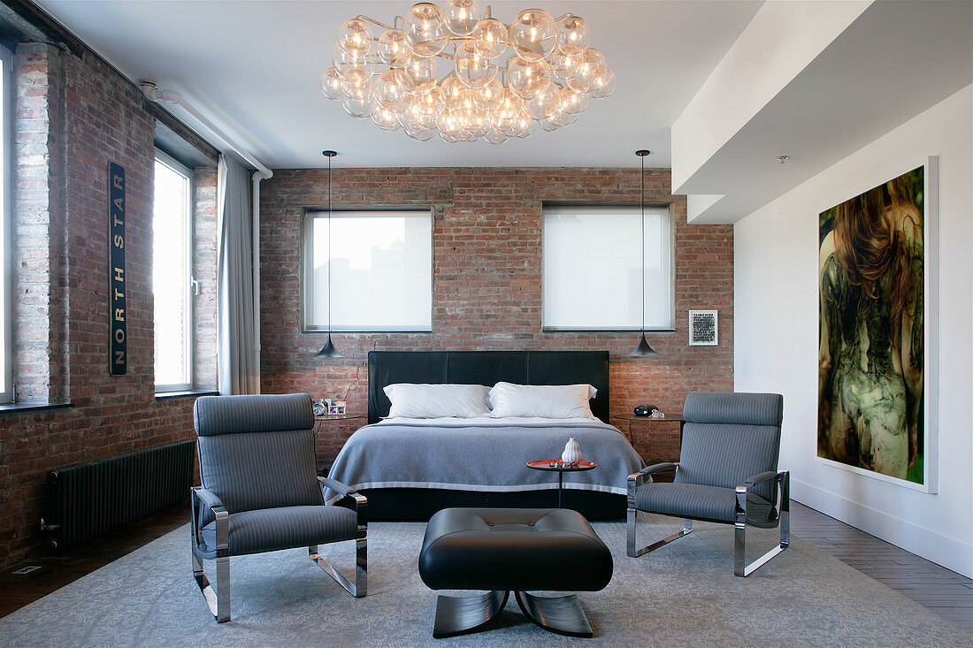 Designer armchairs in front of bed in bedroom with brick walls