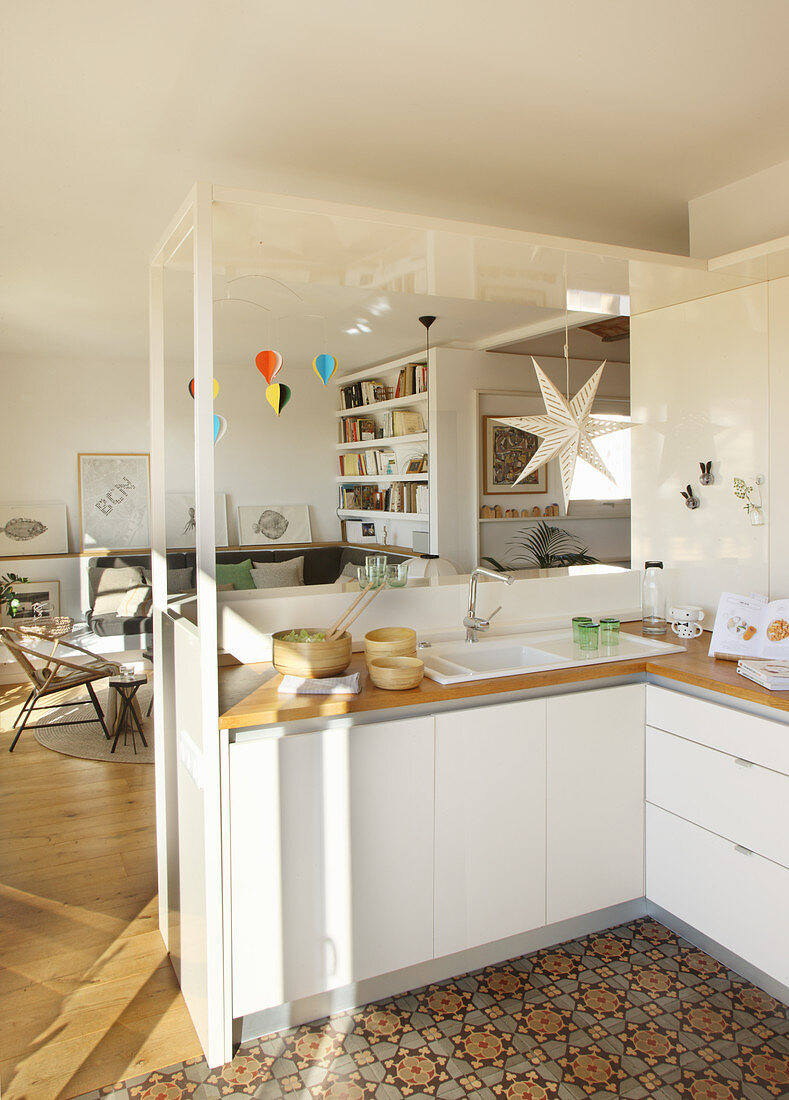 Open-plan kitchen and living room with patterned floor tiles in kitchen area