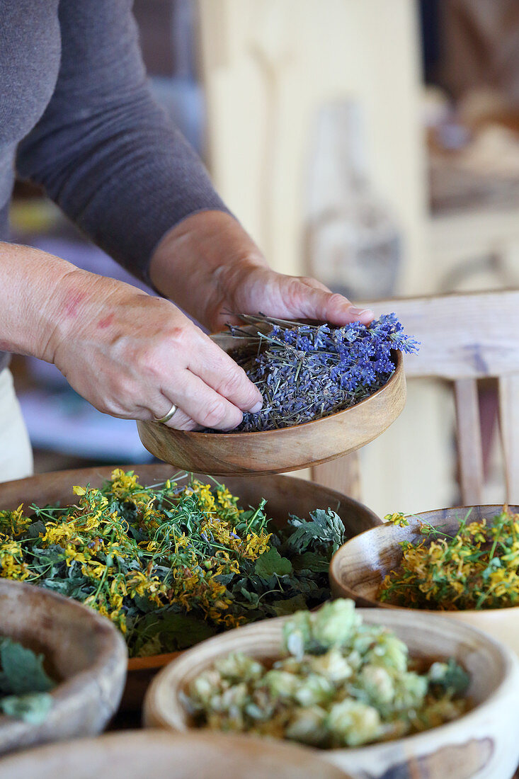 Wooden bowls of dried flowers for making homemade herbal tea