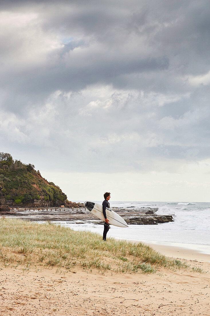 Surfer mit Surfbrett am Coledale Strand (Coal Coast, New South Wales, Australien)