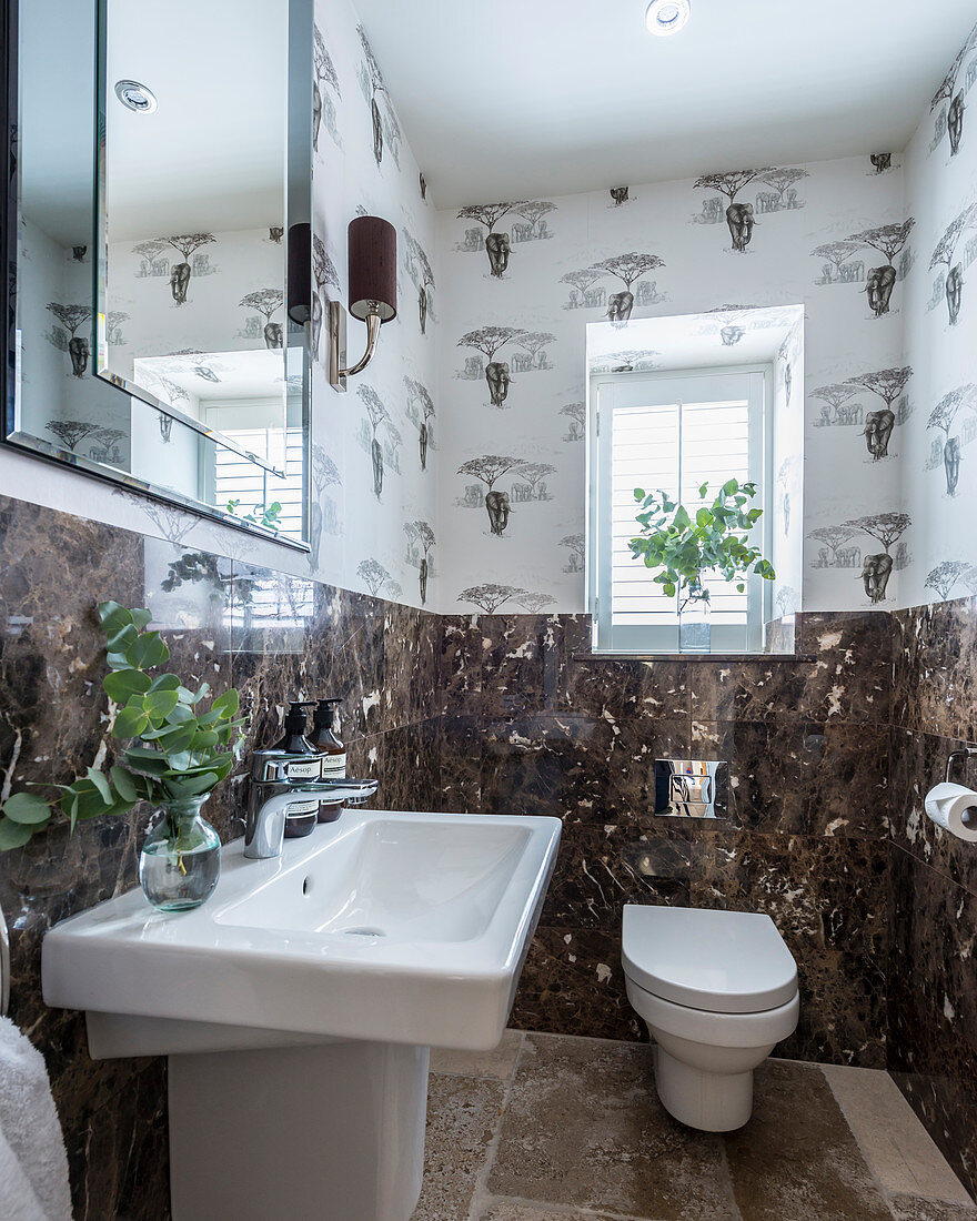Wallpaper with savanna pattern and dark marble wall tiles in guest toilet