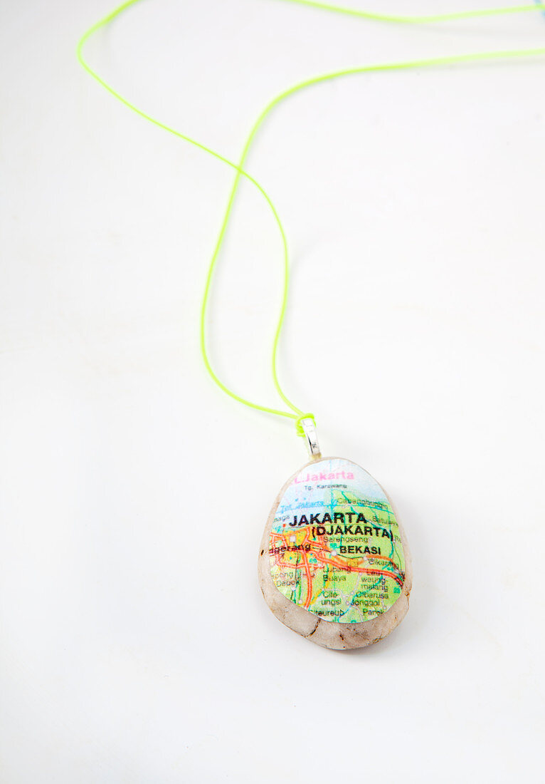 Pendant made from pebble covered with section of map