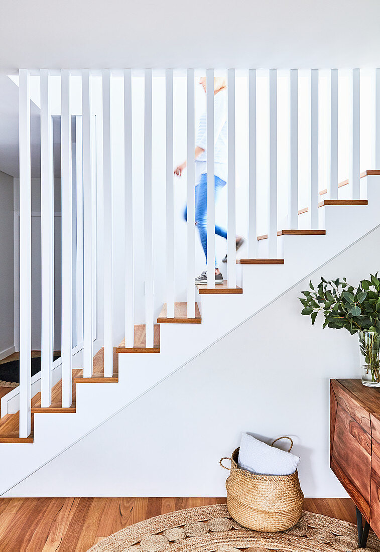 Staircase with straight white balusters, vase of leaves on sideboard and basket on floor