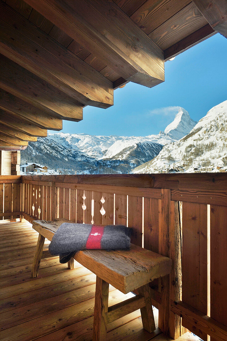 Blanket on bench on chalet balcony with panoramic view of mountains