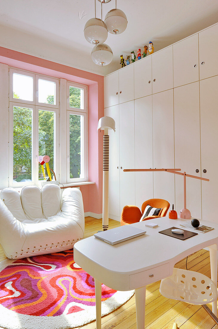 White designer armchair, cupboards and desk in study