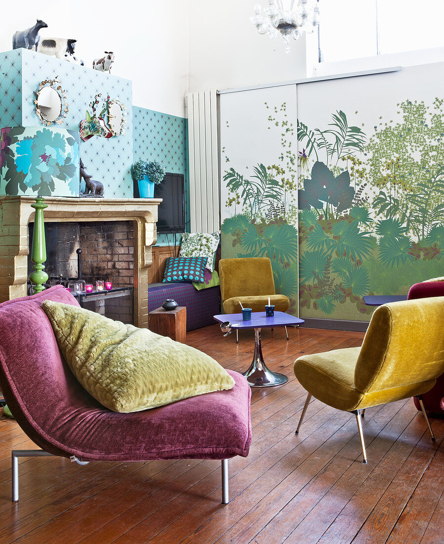 Velvet easy chairs in front of old fireplace and sliding element with plant motif