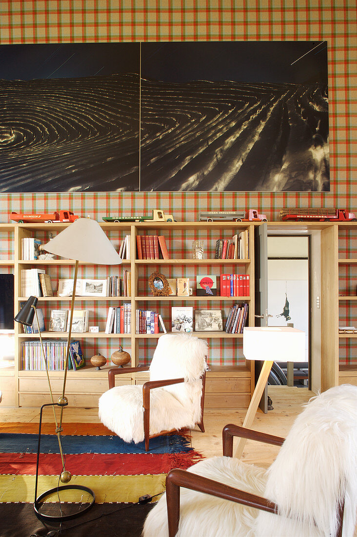 Armchairs and wooden shelves on tartan wallpaper in converted loft
