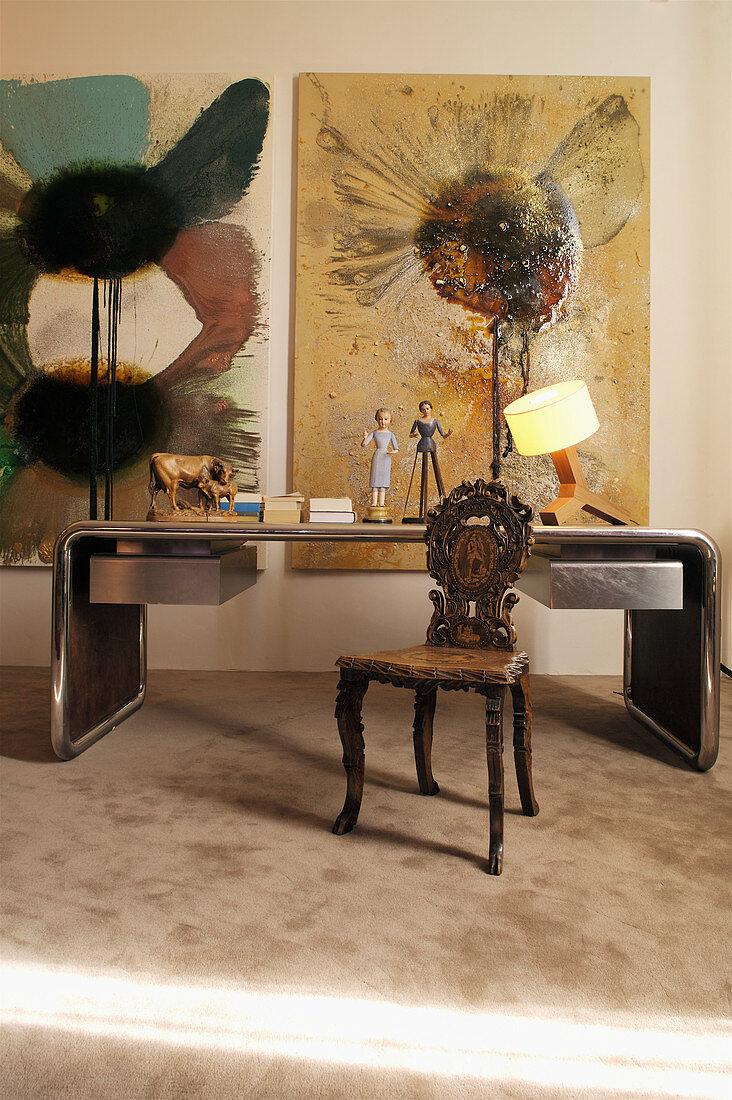 Schreibtisch mit Metallrahmen, antiker Holzstuhl mit Schnitzerei und moderne Kunst an der Wand