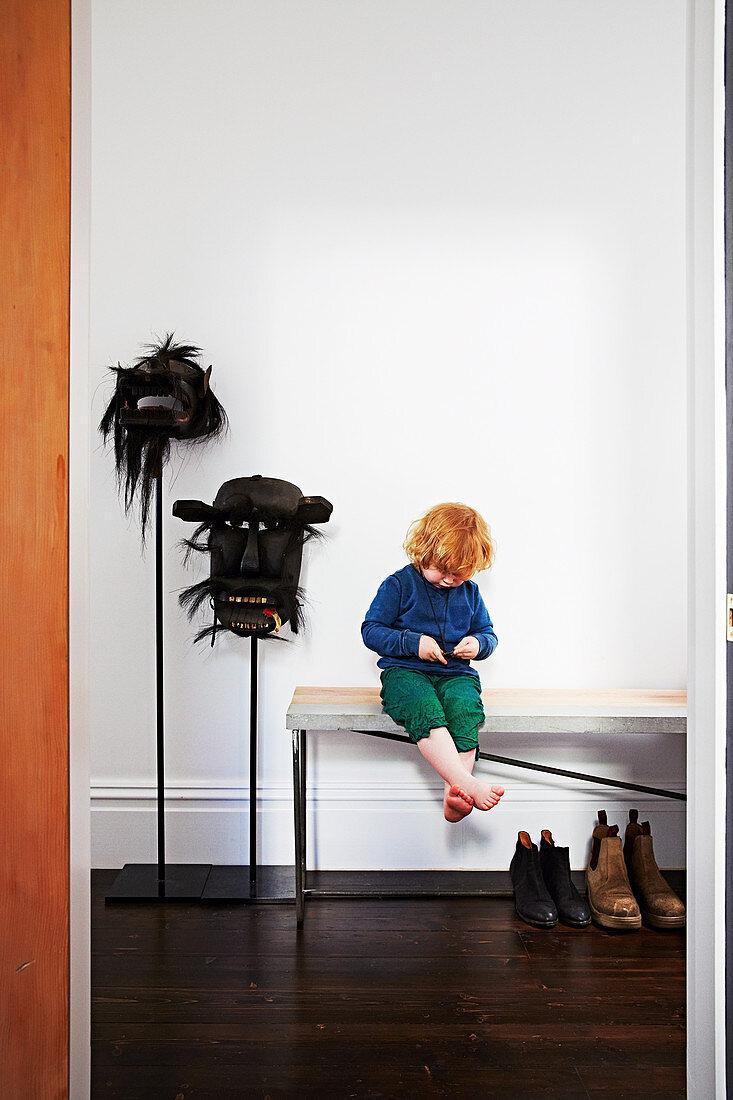 Kleinkind auf Bank sitzend, daneben folkloristische Masken