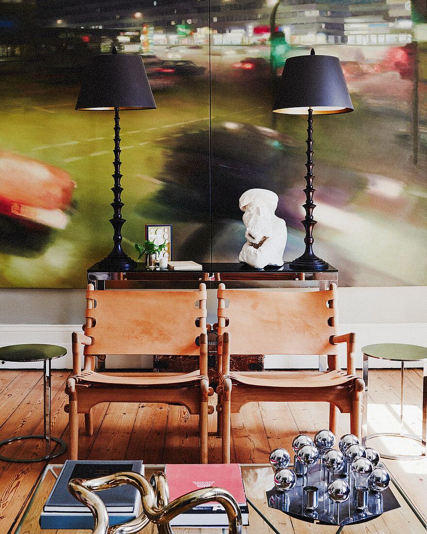 Two leather chairs and console table in front of large artwork