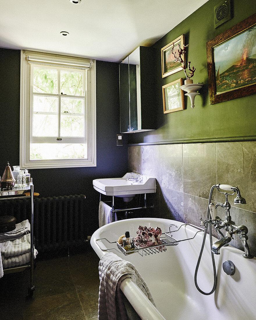 Vintage-style furnishings in dark bathroom with sash window