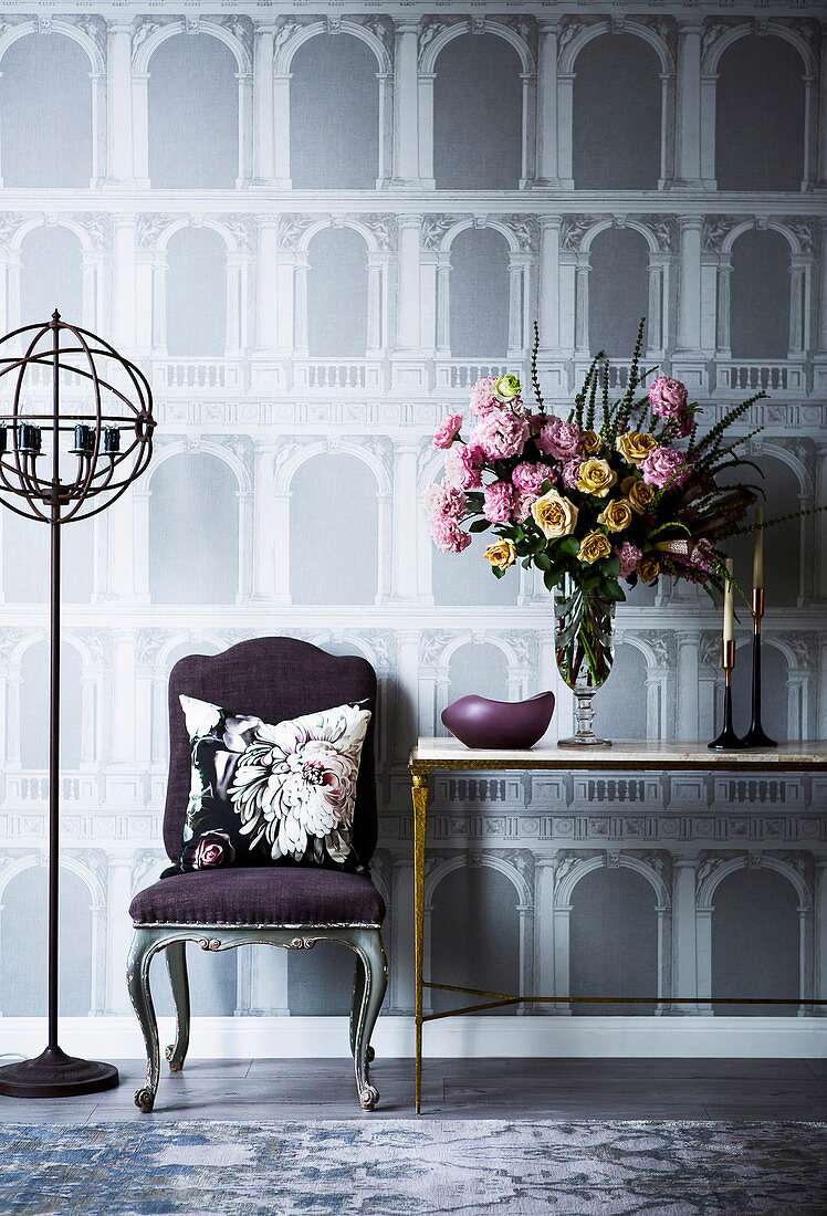 Upholstered chair and console table against wallpaper with architectural motif
