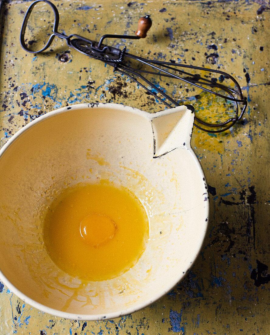 Egg yolk in vintage bowl and whisk