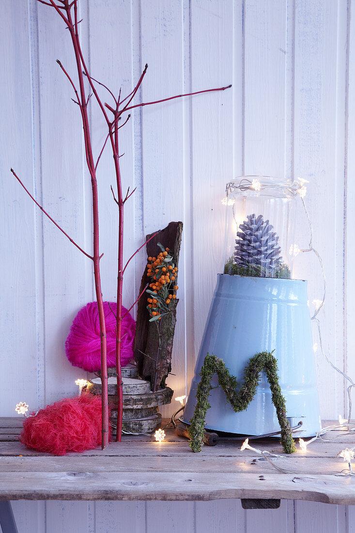 Creative wintry arrangement of natural materials, fairy lights and zinc bucket