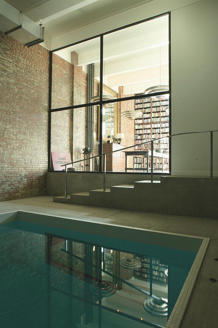 Blick vom Schwimmbecken durch Glaswand ins Wohnzimmer