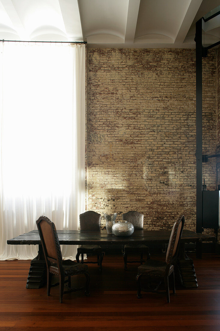 Dark dining table and antique chairs in industrial building