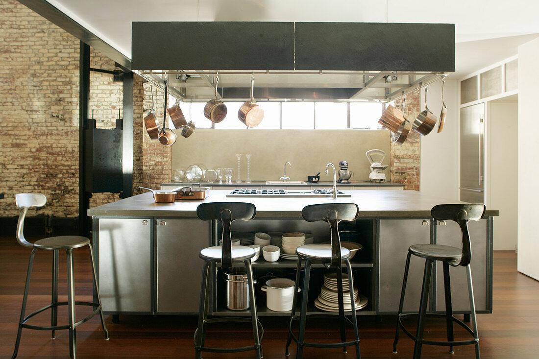 Schwarze Barhocker an einer Kücheninsel im Industriestil