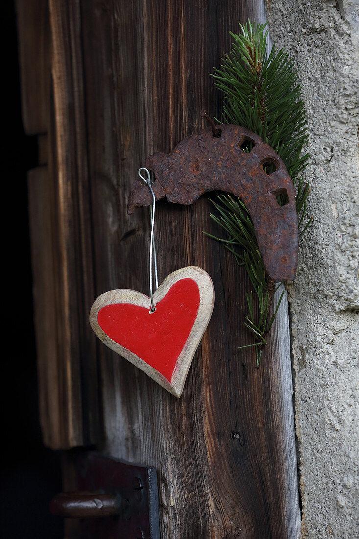 Heart pendant hung on wooden door