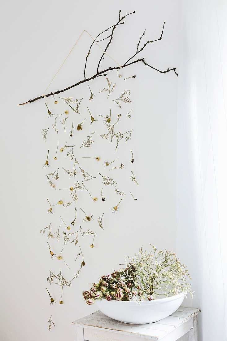Mobile made from dried flowers hung from twig