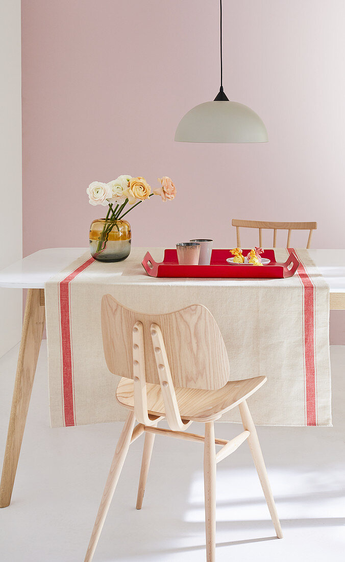 A natural-coloured linen table runner with a red border on a dining table