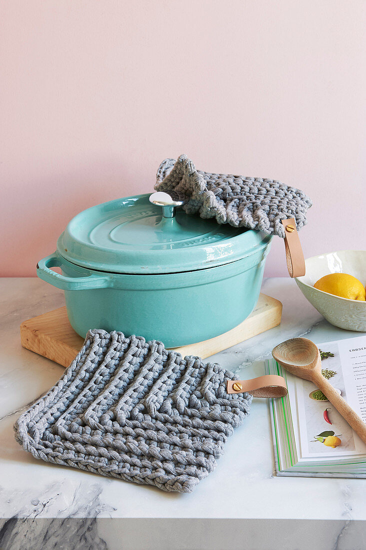 A crocheted pot holder with a leather loop