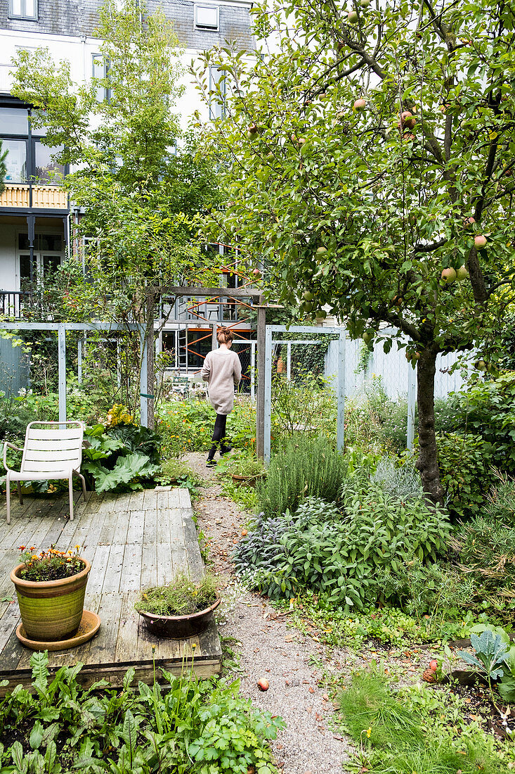 Woman walking through cottage garden with weathered terrace