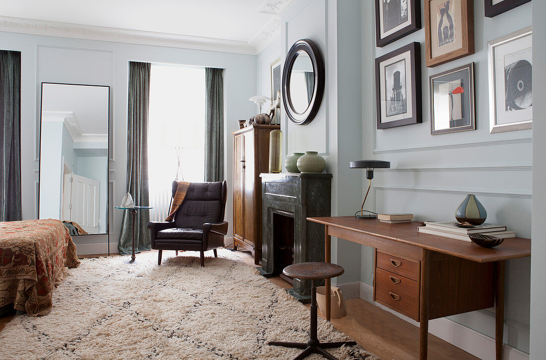 Teal desk, marble fireplace and vintage leather armchair in spacious bedroom