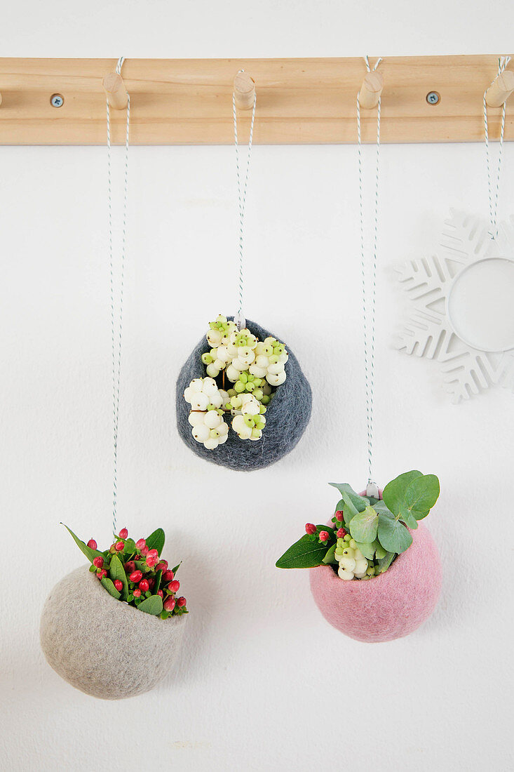 Sprigs of berries in round felt cocoons hung from peg board