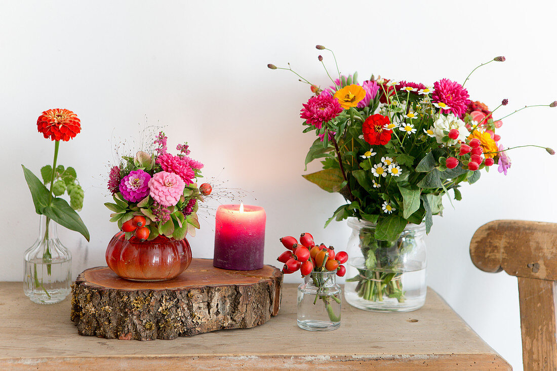 Late summer bouquets, log board and candle on wooden table