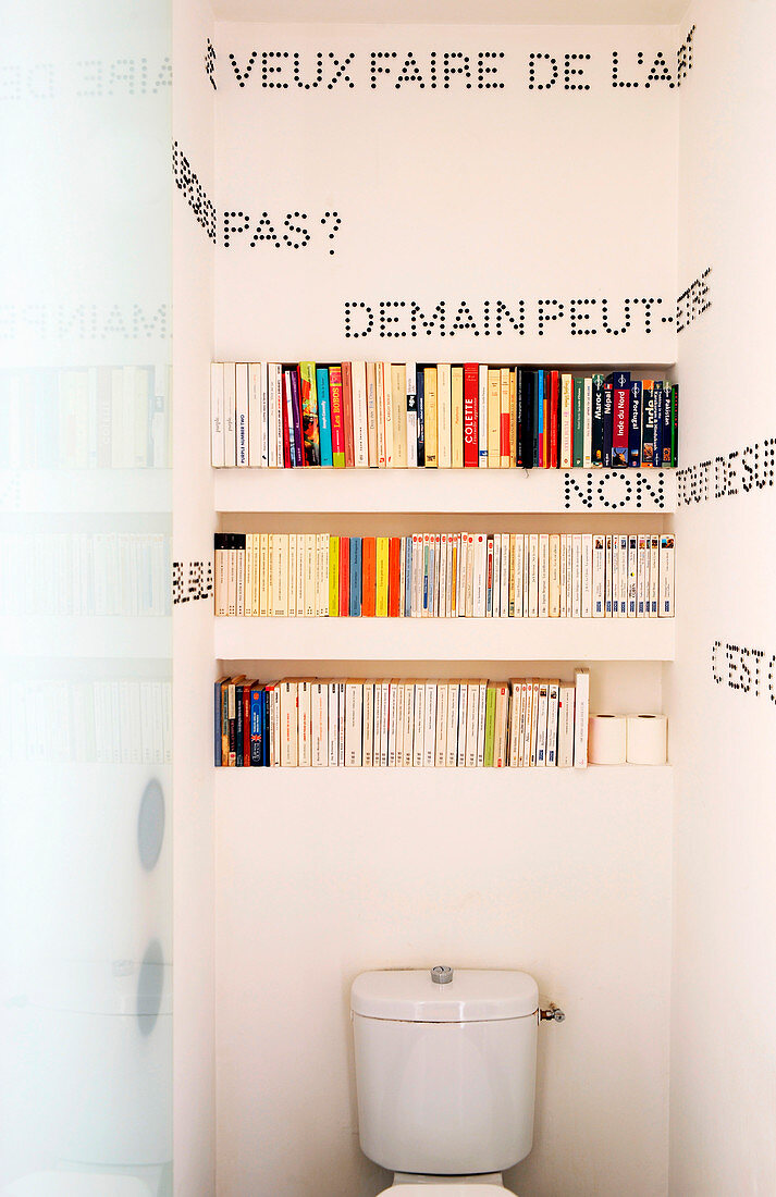Bookshelves and mottoes written in black drawing pins on walls of toilet