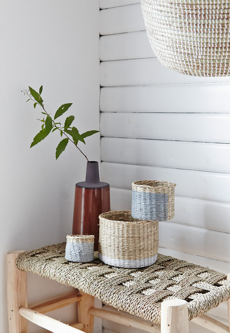 Decorative baskets made from natural fibres on stool with woven seat