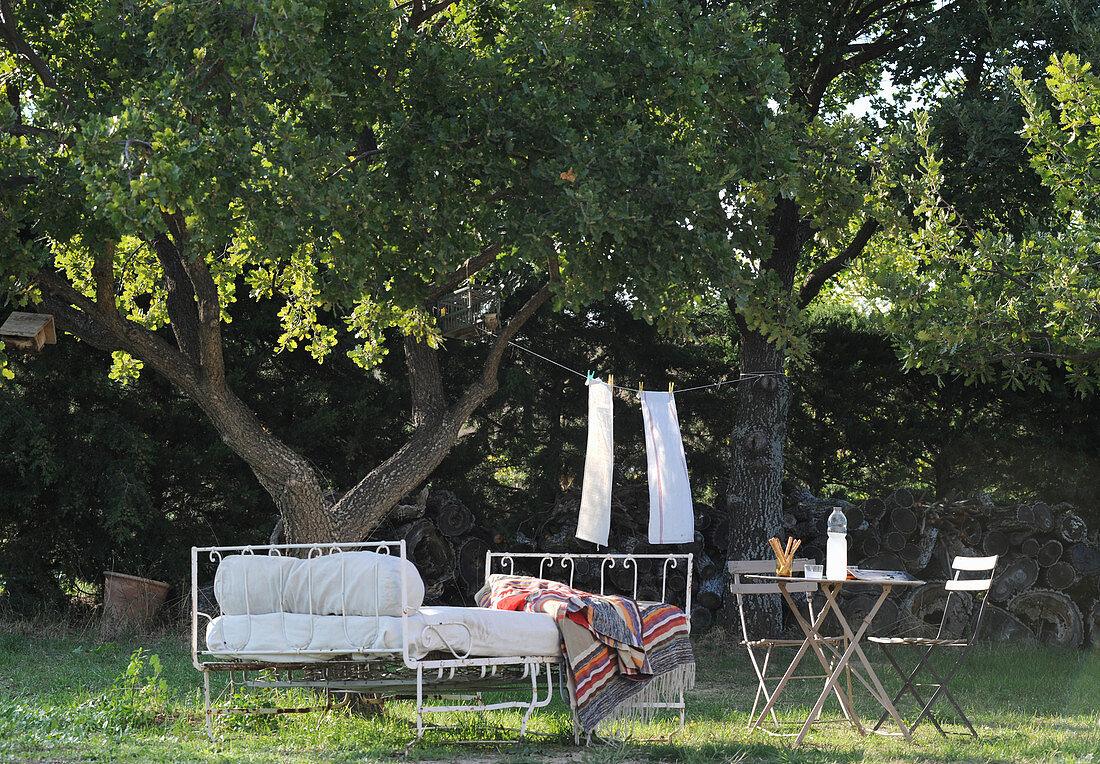 Metal bed and garden furniture below tree in Mediterranean garden