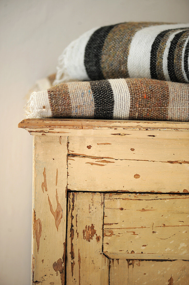 Folded woven blankets on top of cupboard with peeling paint