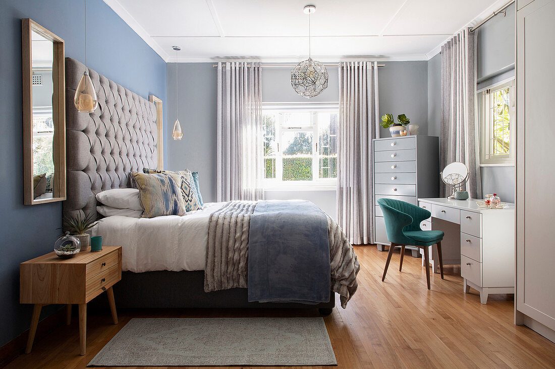Double bed with high, button-tufted headboard and dressing table in bedroom in shades of pale grey and brown