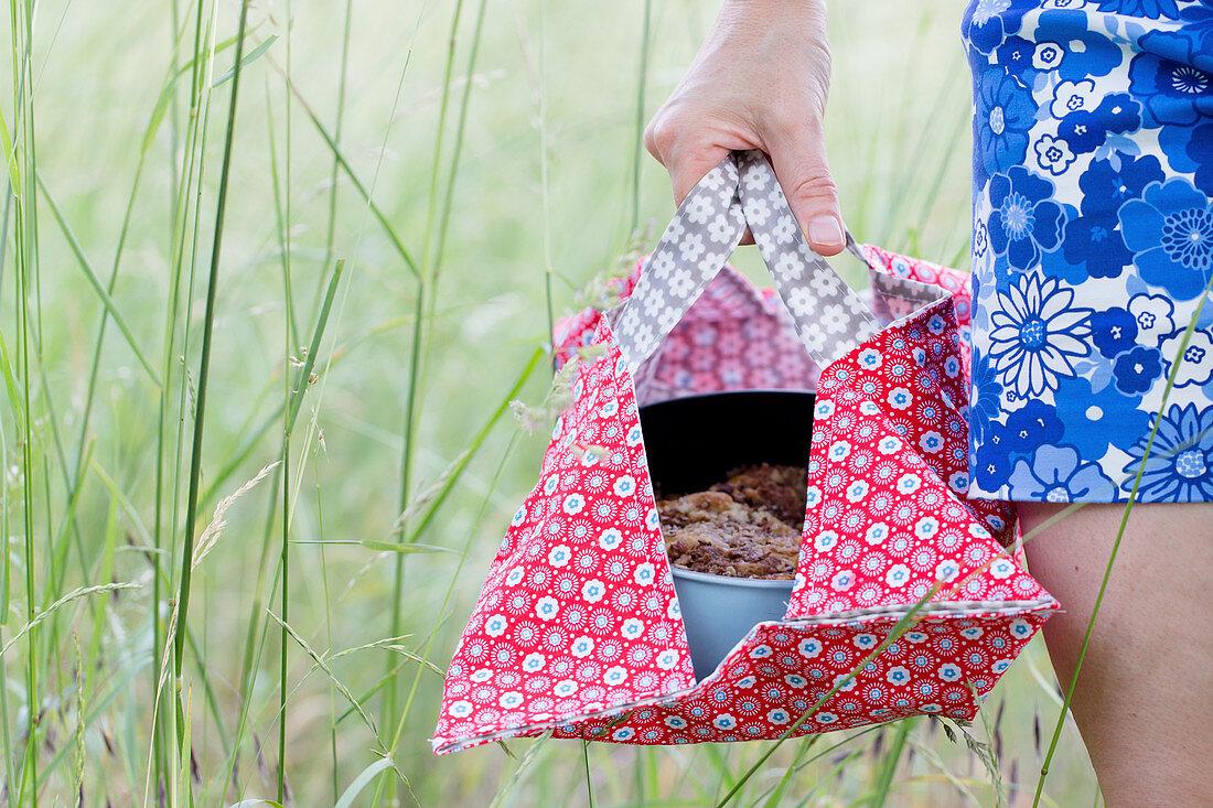 Frau trägt Kuchen mit Springform in DIY-Kuchentasche aus Wachstuch