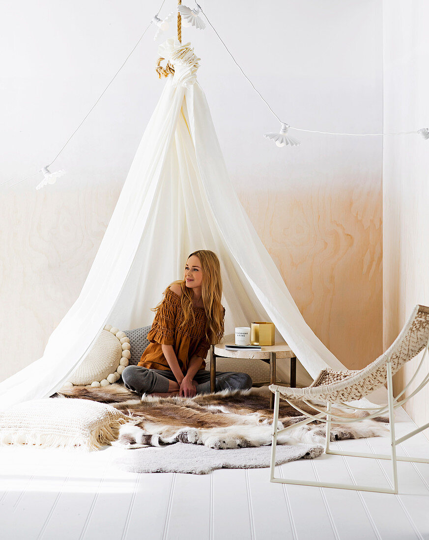 Woman is sitting under the hanging tent with furs and coffee table