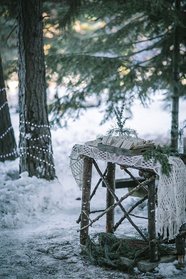 Macrame runner and gifts on small wooden table in snowy woods