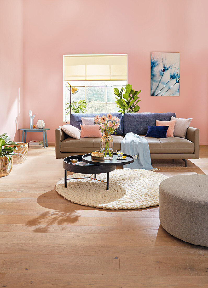A leather sofa and a round, pivoting coffee table in a living room with pink walls