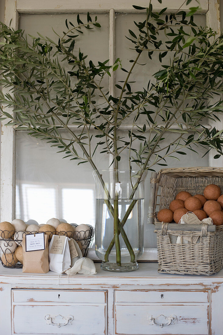 Olive branches in vase and basket of bath bombs