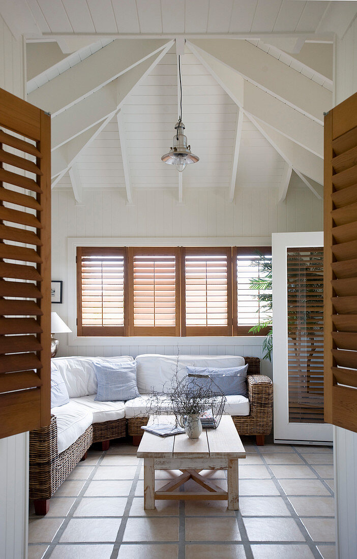 Wicker sofa in beach-house-style living room with high ceiling and tiled floor
