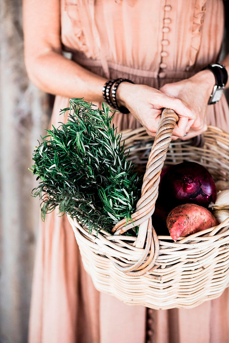 Woman in nostalgic dress carries basket with sprigs of rosemary and harvest