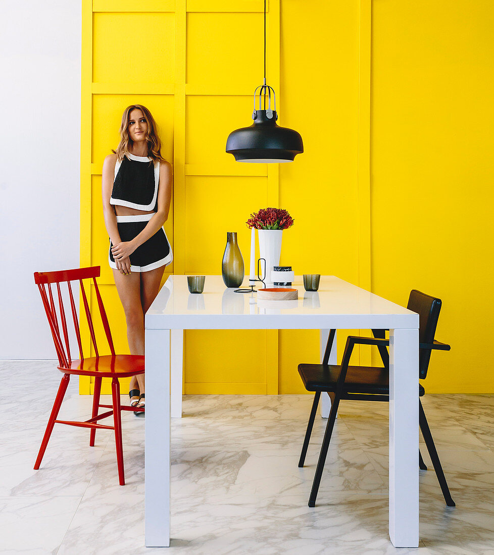 White table and chairs in the dining area, young woman against yellow cassette wall