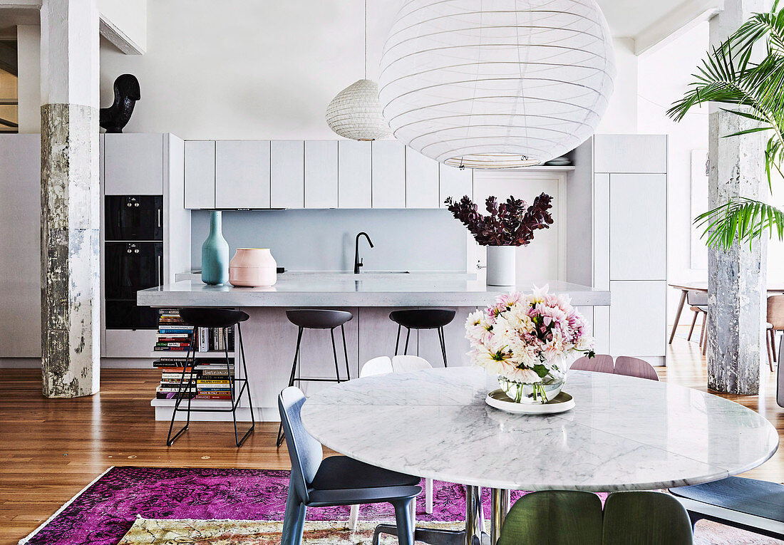 Open living room with modern white kitchen, breakfast bar and round marble dining table