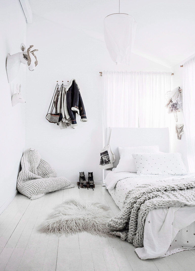 Feminine bedroom in white with beanbag and fairytale animal trophies as wall decoration