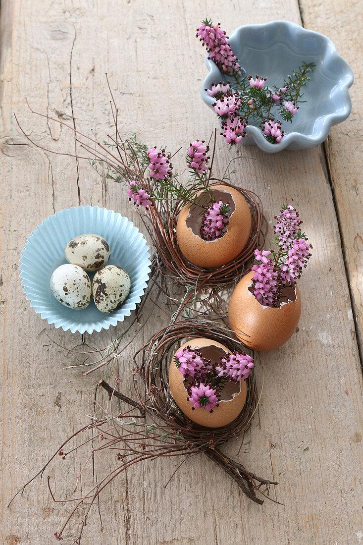 Ausgepustete Eier als kleine Blumenvasen mit lila Heideblüten zu Ostern