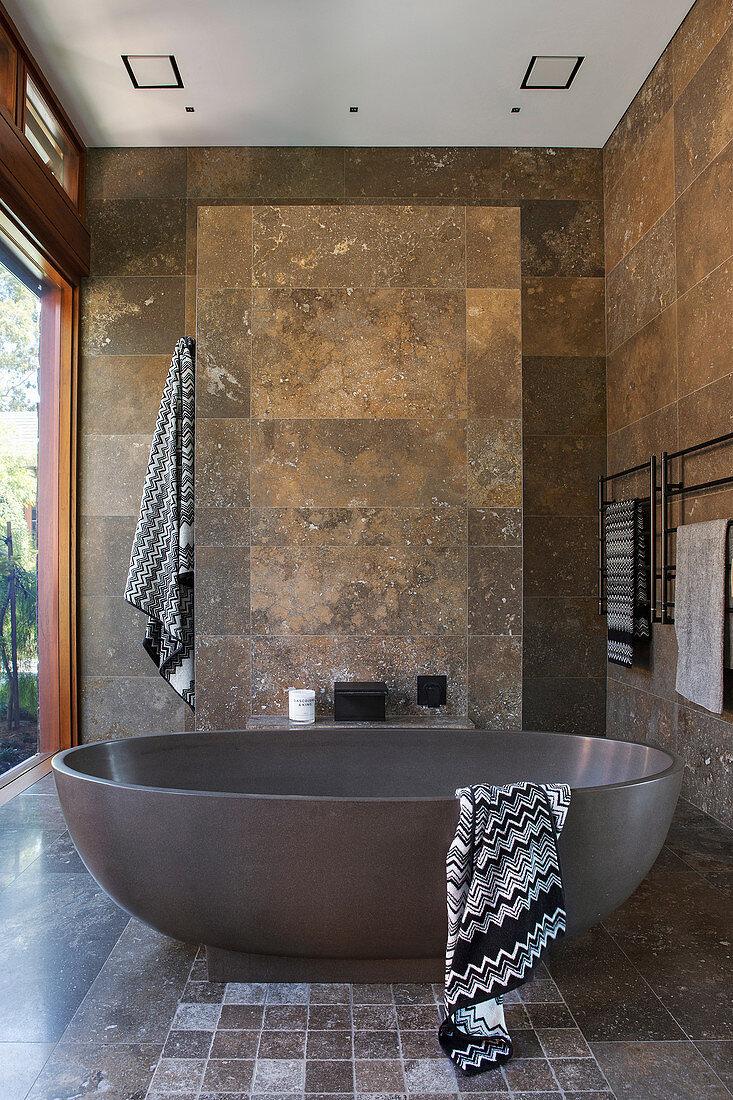 Freestanding bathtub in the bathroom with travertine tiles