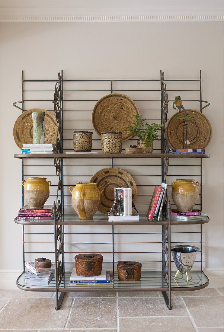 Collection of ceramics, raffia dishes and books on metal shelves